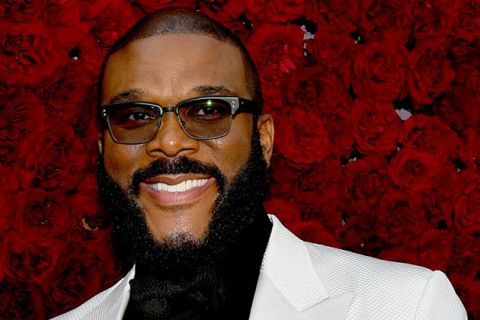 Tyler Perry. Black man with low hair, beard, glasses, wearing white tux jacket and black shirt.