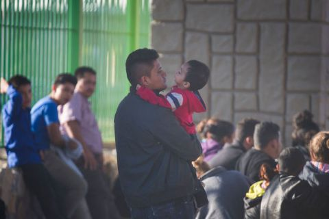 A father at the Southern Border hold his young son in his arms.