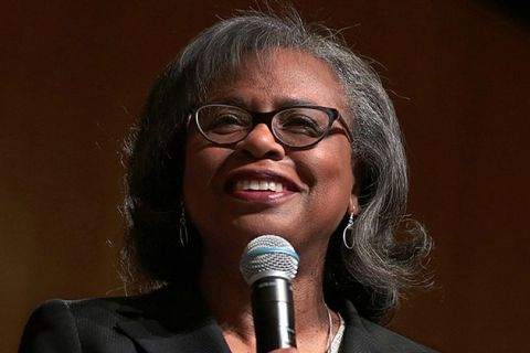 Anita Hill. Older Black woman with gray hair and glasses holding microphone.