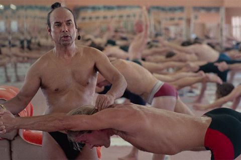Bikram Choudhury. Indian man in yoga classroom giving instructions to practitioner, wearing black underwear.