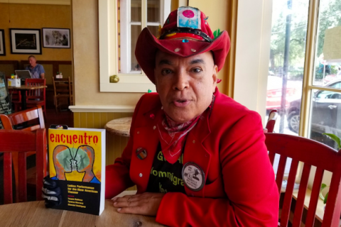 "A Equadorian man wears a red cowboy hat and matching suit and holds up a book titled ""Encuentro."""