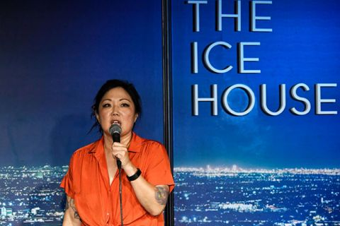 "Margaret Cho. Korean American woman wearing orange top holding microphone in front of sign reading ""The Ice House."""