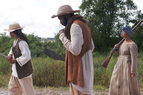 Slave Rebellion Reenactment. Two men and one woman dressed in period clothing and carrying weapons.