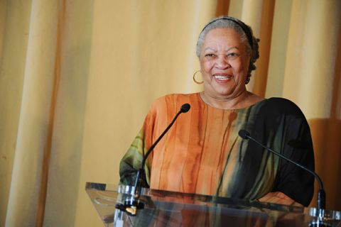 Toni Morrison. Black woman with gray hair standing behind podium wearing colorful dress.