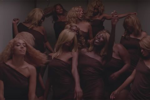 """When I Get Home"" video. Several Black women wearing blonde wigs and matching brown outfits."