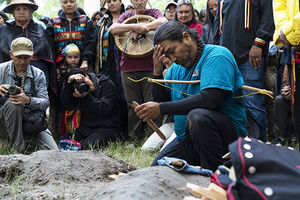 A Native man wearing a turquoise t-shirt prays while a group watches