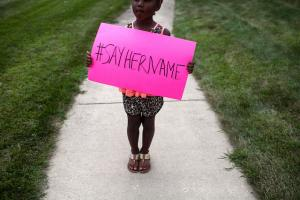 5-year-old holds up #SayHerName poster at Sandra Bland funeral