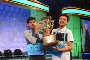 Two boys hold a large golden trophy.