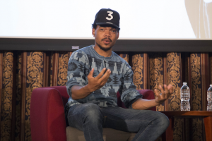 "Chance the Rapper in blue sweater and blue jeans, wearing black baseball cap with white ""3"" on the front, sitting on red chair with projection screen and brown and black pattern behind him"