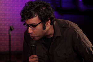 Comedian Hari Kondabolu in brown shirt with purple/pink background