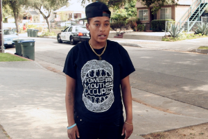 Jasmine Richards in black shirt and black backwards hat, standing by street with green trees and brown and white houses in background, black and white police car in background