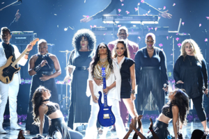 Sheila E. in white outfit and holding purple guitar, surrounded by background performers