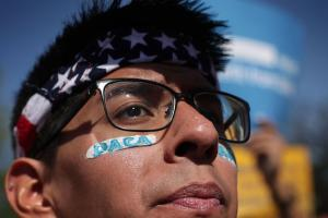 "Pro-immigration activist Omar Martinez demonstrates in front of the SCOTUS wearing an U.S. flag bandana and the word ""DACA"" painted on his face."