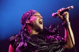 D'Angelo in black outfit, holding microphone in front of blue background , covered in purple light
