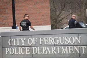 "Two police officers dressed in black stand behind a sign that says ""City of Ferguson Police Department."""
