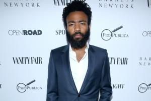 Donald Glover in white dress shirt and navy blazer