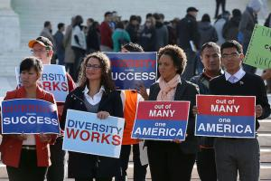 "Seven protestors hold red, white and blue signs that say ""Diversity equals success,"" and ""Out of many, one America"" and ""Diversity works."""