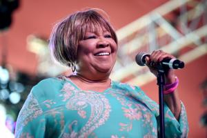 Mavis Staples in blue-and-pink paisley shirt, holding black microphone