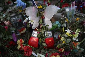 Red boxing gloves and a portrait of Muhammad Ali set amidst green floral arrangements