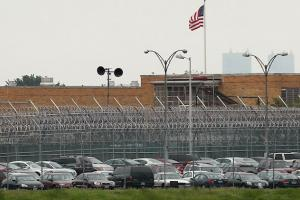 Rikers Island prison, fences with barbed wire, brown building, American flag