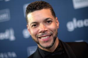 Wilson Cruz in Black suit and tie with blue background