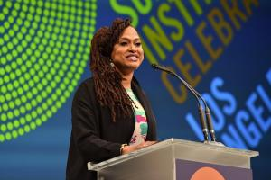 Ava DuVernay in multicolored shirt under black jacket, speaking at clear podium with black microphone