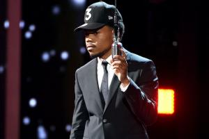 Chance the Rapper in black baseball cap, black suit with black tie and white shirt