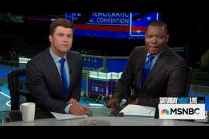 Colin Jost and Michael Che in black suits with blue ties