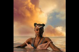 Jamila Woods in water with blue and pink clothing, orange-hued background