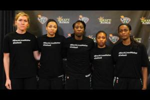 "Five New York Liberty players wearing black shirts reading ""#BlackLivesMatter"" and ""#Dallas5"" in white text"