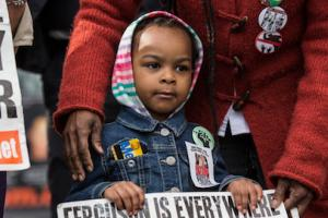 A little Black girl in a striped hoodie holds up a sign during a protest