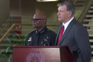 A Black man in a police uniform stands beside a White man in a suit behind a podium