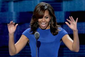 Black woman in blue dress stands in front of a microphone