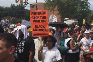 Protestors hold signs