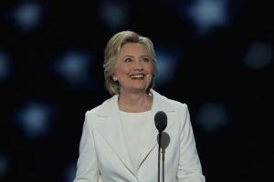 White woman in white suit smiles and looks heavenward