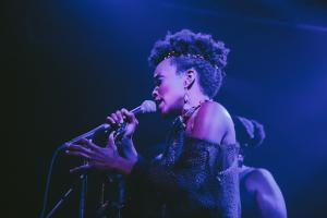 Jamila Woods in purple- and blue-hued light