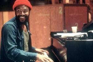 Marvin Gaye in denim jacket and red hat at black piano