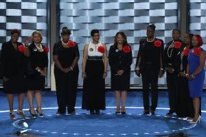 Nine black women stand in a line on a stage