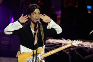 Prince in black-and-white shirt, holding light brown guitar