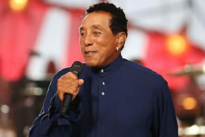 Smokey Robinson in navy sweater, holding black and gray microphone