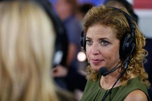 Woman with blonde hair wears black headphones and green top