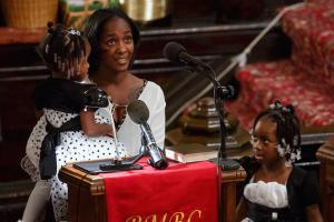 Black woman stands in church pulpit holding one young Black girl with another standing beside her