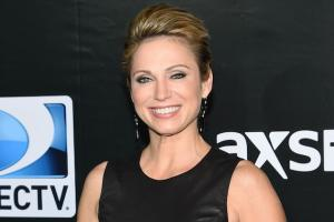 Amy Robach in black dress against black background with logos