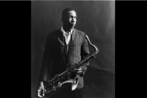 John Coltrane in black-and-white image holding saxophone