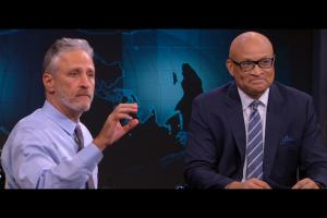 Jon Stewart in light blue dress shirt, Larry Wilmore in navy suit