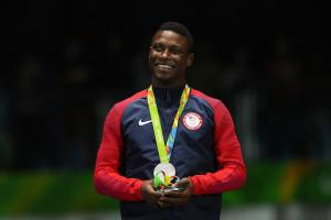 Daryl Homer in navy and red warm ups, wearing silver medal on green ribbon