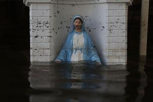 A Virgin Mary statue is seen in front of a flooded home on August 18, 2016, in St Amant, Louisiana.