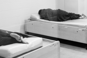 Women sleep in beds in an institutional setting