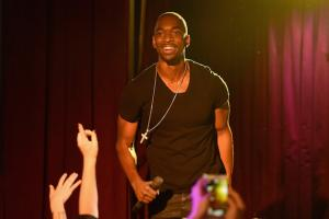 Jay Pharoah in black t-shirt on stage with purple-hued background
