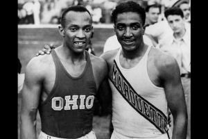 Black-and-white image of Jessie Owens and Ralph Metcalfe in jerseys and shorts